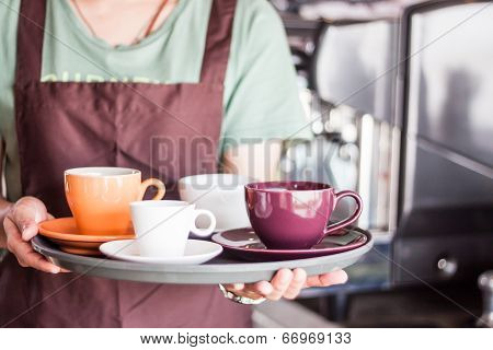 Coffee Shop Owner Serving Set Of Freshly Brewed Coffee