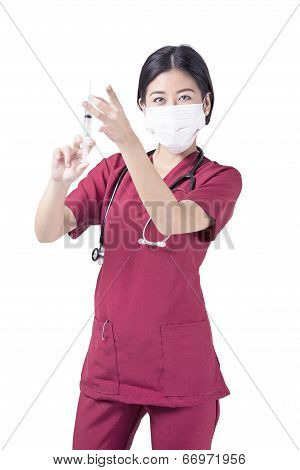 Female nurse flicking a syringe