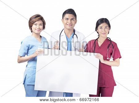 Smiling nurses holding a white board