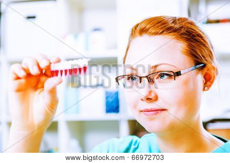 Female tech or scientist works with pipette in biological laboratory. Genetic research is the study of human, animals or plant  DNA