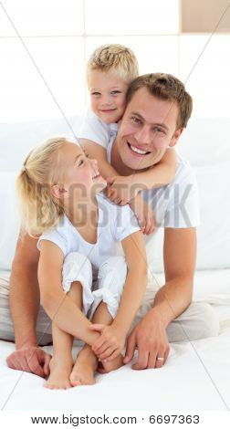 Caring Father With His Children Sitting On Bed