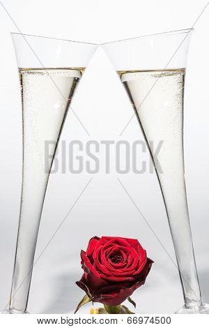 champagne or sparkling wine in a champagne glass with red rose. symbolic photo for celebration, wedding anniversary, valentine's day, birthday.