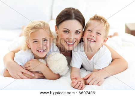 Happy Mother And Her Children Lying On A Bed