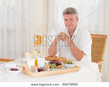 Senior Mature Man Sitting Down To A Healthy Breakfast Looking At Camera