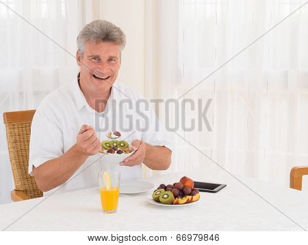 Laughing Mature Man Eating A Healthy Cereal Breakfast