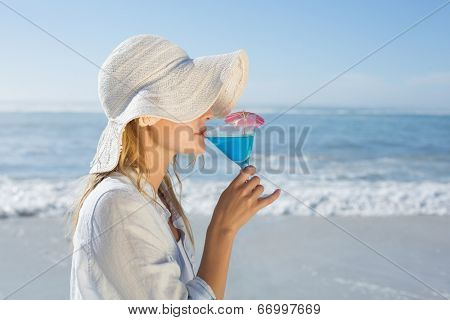 Smiling blonde relaxing by the sea sipping cocktail on a sunny day
