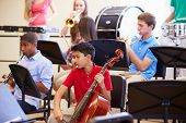 stock photo of trumpet  - Pupils Playing Musical Instruments In School Orchestra - JPG