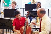 stock photo of cello  - Boy Learning To Play Cello In High School Orchestra - JPG