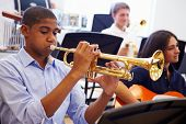 stock photo of trumpet  - Male Pupil Playing Trumpet In High School Orchestra - JPG