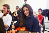 foto of orchestra  - Female Pupil Playing Guitar In High School Orchestra - JPG