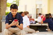 stock photo of playground school  - Male High School Student Using Phone On School Campus - JPG