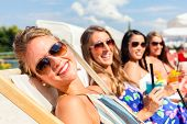 pic of sun-tanned  - Four woman lying on beach lounger - JPG