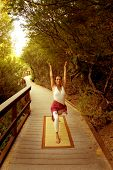 pic of yoga mat  - Woman in the yoga Warrior 1 posture on a nature pathway - JPG