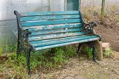image of neglect  - Weathered and neglected garden bench with overgrown weeds - JPG