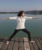foto of virabhadrasana  - Young yogi caucasian woman is doing Warrior pose by lake in nature. ** Note: Soft Focus at 100%, best at smaller sizes - JPG