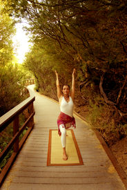 foto of yoga mat  - Woman in the yoga Warrior 1 posture on a nature pathway - JPG