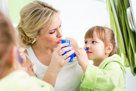 stock photo of douche  - mother and kid with neti pot ready for nasal irrigation or douche - JPG