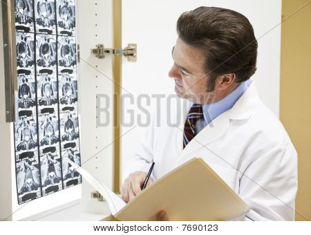 Doctor Making Notation In Chart