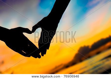 silhouettes of young loving couple on bright sunset sky and sea background making heart shape with their hands