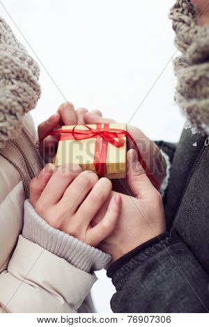 Man giving a little gift box to his girlfriend