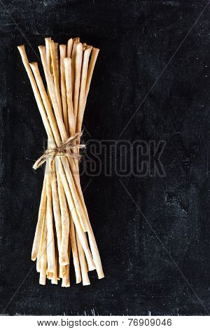 top view of breadsticks grissini torinesi on blackboard background