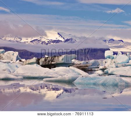 Early summer morning. Icebergs and ice floes are reflected in smooth water. Ocean ice lagoon