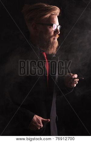 Side view image of a elegant fashion man holding a cigarette in his left hand while the right hand is in his pocket.