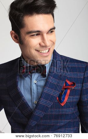 Close up picture of a smart casual fashion man smiling while looking away from the camera.