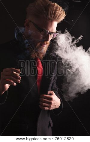 Portrait of a young fashion man pulling his coat while smoking a cigarette, looking down.