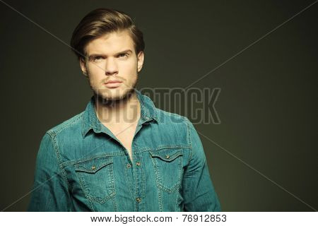 Close up picture of a young fashion man looking away from the camera, thinking.
