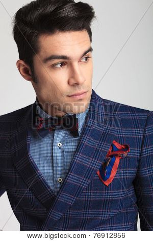 Close up picture of a handsome young fashion man looking away from the camera.