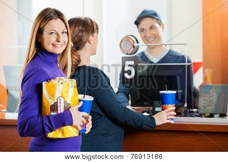 Portrait of beautiful woman holding snacks while friend buying movie tickets from male seller at box office
