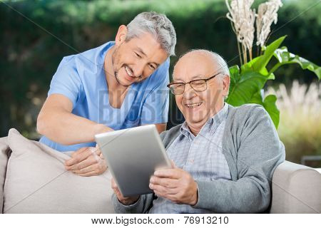Happy male caretaker and senior man using tablet PC at nursing home porch
