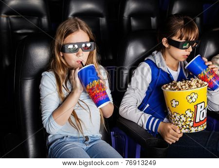 Sisters having snacks while watching 3D movie at cinema theater
