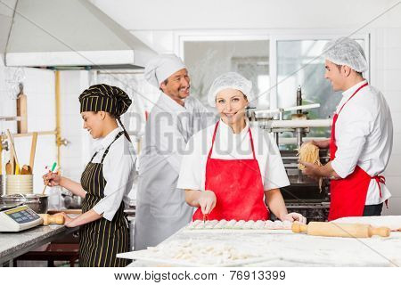 Portrait of confident female chef cutting ravioli pasta at counter with colleagues working in background at commercial kitchen