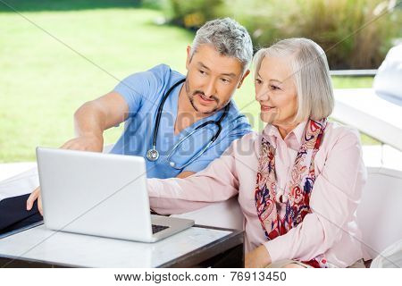Male caretaker assisting senior woman in using laptop at nursing home porch
