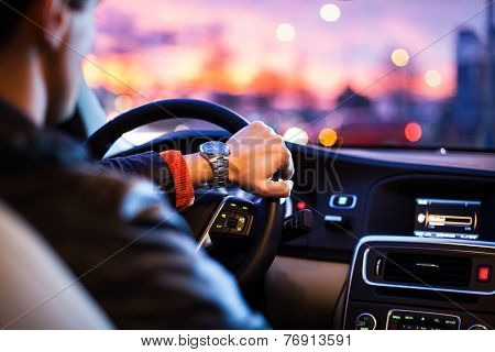 Driving a car at night -man driving his modern car at night in a city (shallow DOF; color toned imag