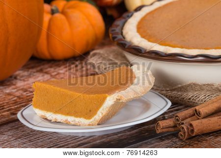Slice Of A Pumpkin Pie And Pumpkins On The Background