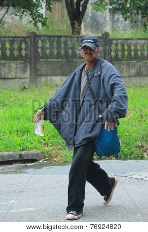 brazilian man with bottle of alcohol walk down the street in Curitiba