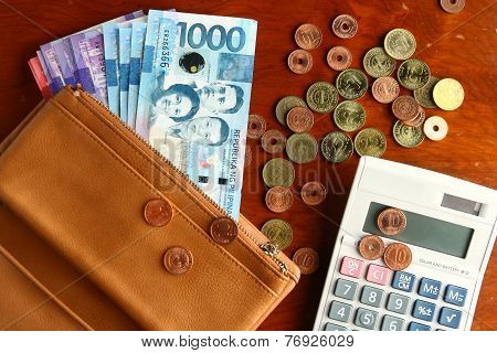 Cash money in a leather wallet, coins and a calculator