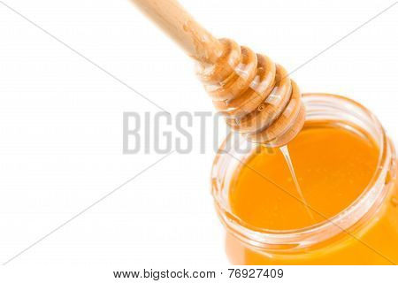 Honey Jar On White Background With Wooden Honey Dipper On Top And Drop Honey