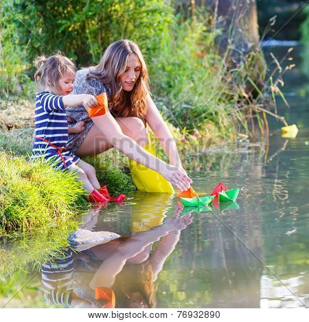 Adorable Little Girl And Her Mom Playing With Paper Boats In A River.