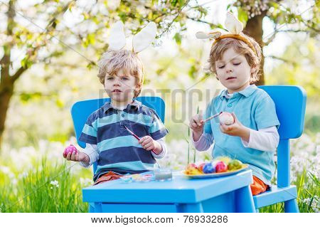 Two Little Children Wearing Easter Bunny Ears, Painting Colorful Egg