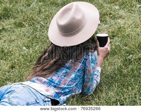 woman resting in grass with cup of coffee