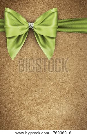 Green bow on texture of paper packaging
