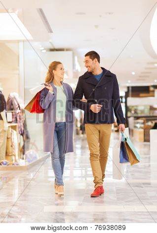 sale, consumerism and people concept - happy young couple with shopping bags walking and talking in mall