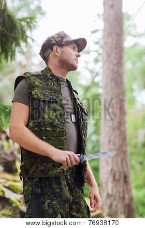 hunting, war, army and people concept - young soldier, ranger or hunter with knife in forest