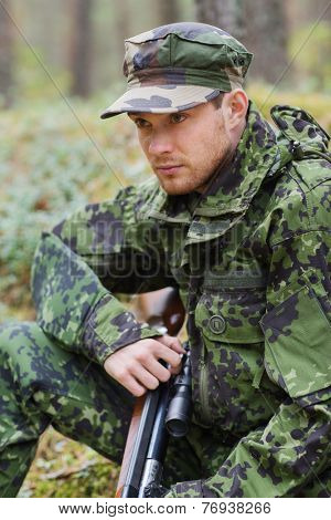 hunting, war, army and people concept - young soldier, ranger or hunter with gun sitting in forest