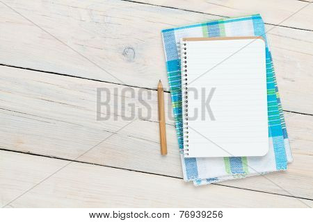 Notepad over kitchen towel on wooden table with copy space