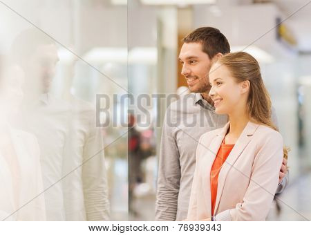 sale, consumerism and people concept - happy young couple looking to shop window in mall
